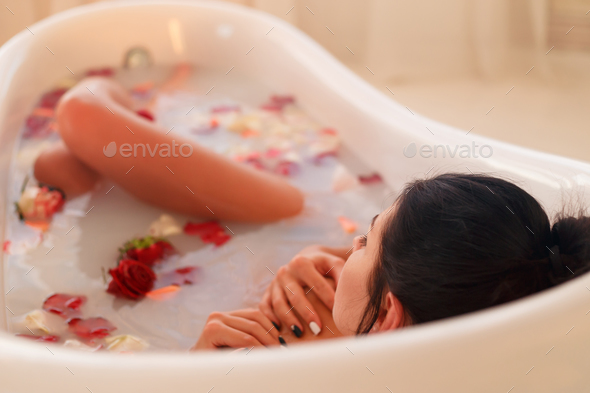 Brunette woman relaxing in the milk bath. - Stock Photo - Images