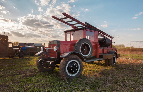 Old retro fire truck with wooden case on the field - Stock Photo - Images