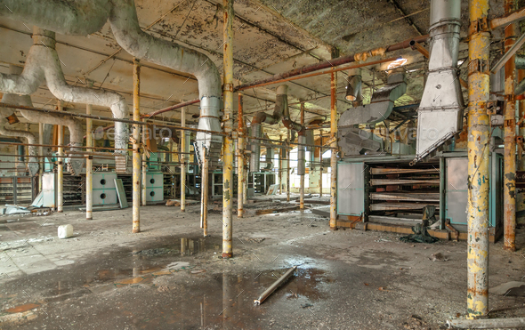Destroyed production room of an old abandoned textile factory with remains of broken equipment - Stock Photo - Images