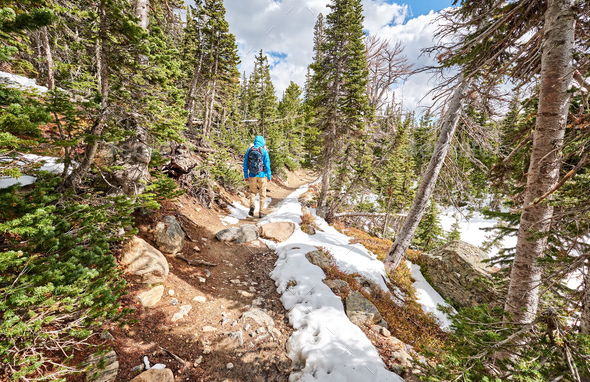 Tourist with backpack hiking on snowy trail - Stock Photo - Images