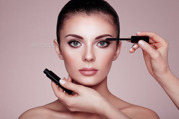 Beautiful brunette woman paints the eyelashes - Stock Photo - Images