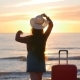 Young Woman Traveler with a Suitcase on the Beach on Sunset - VideoHive Item for Sale