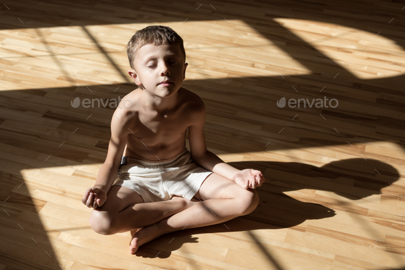 Charming little boy is while doing yoga at home - Stock Photo - Images
