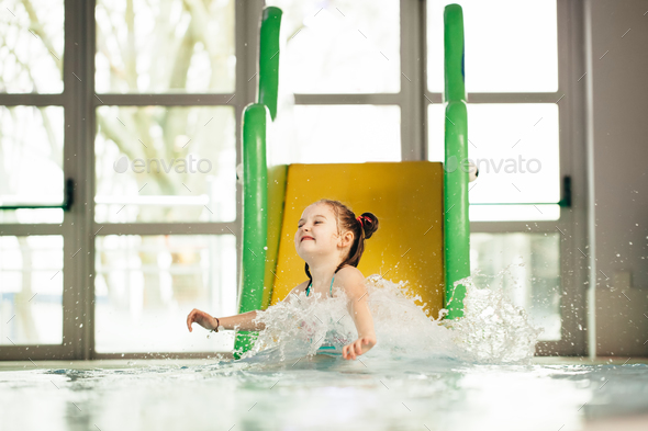 Little girl sliding down the water slide - Stock Photo - Images