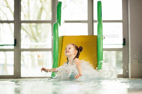Little girl sliding down the water slide - Stock Photo - Images