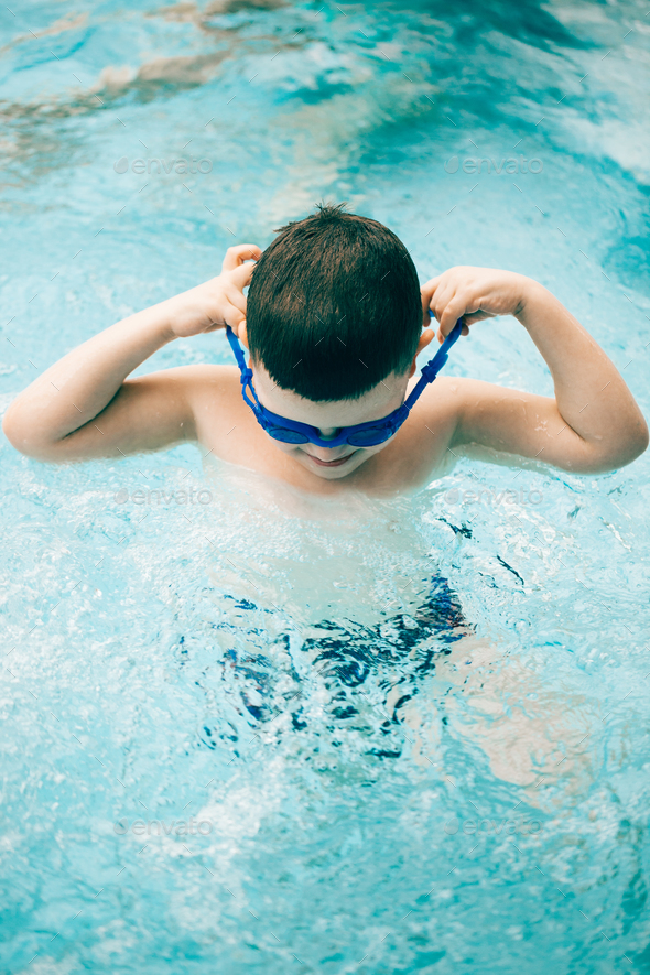 Boy in a swimming pool with diving goggles - Stock Photo - Images