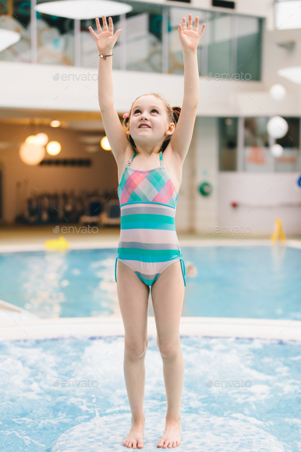 Little girl standing on the floor in a pool - Stock Photo - Images