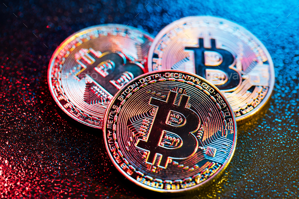 Three bitcoin coins in a colorful lighting. - Stock Photo - Images