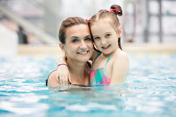 Young girl and her mother hugging in the pool. - Stock Photo - Images
