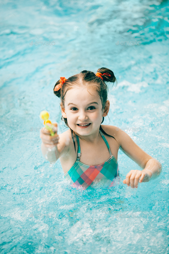 Girl in a swimming pool with a water pistol - Stock Photo - Images