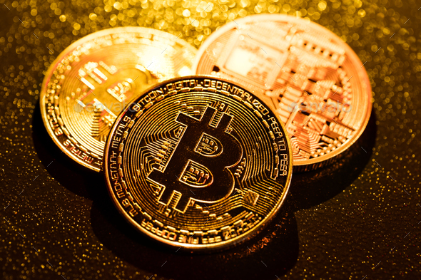 Three golden bitcoin coins on black background. - Stock Photo - Images