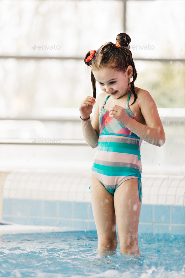 Little girl with wet hair standing in a kid's pool. - Stock Photo - Images