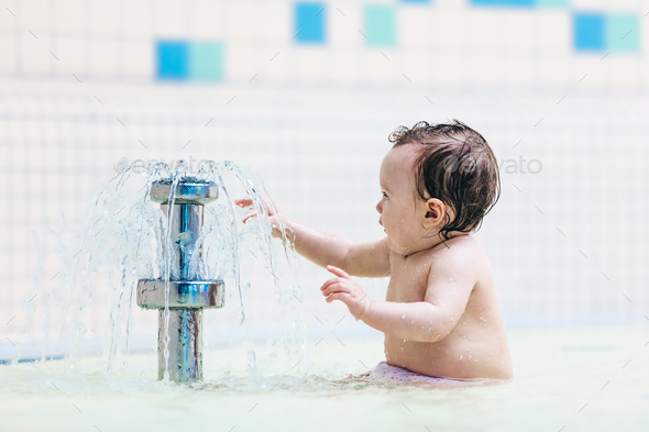 Toddler sitting in front of little fountain. - Stock Photo - Images