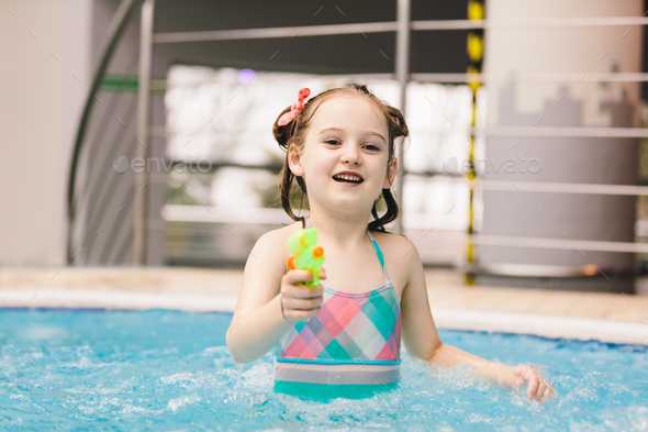 Little girl with water pistol in a swimming pool. - Stock Photo - Images