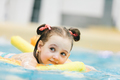 Little girl swimming with a yellow noodle in a pool. - PhotoDune Item for Sale