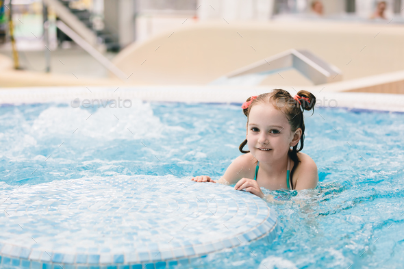 Little happy girl playing in a jacuzzi. - Stock Photo - Images