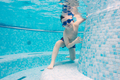 Boy playing in a swimming pool with goggles on - PhotoDune Item for Sale