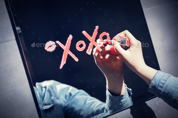 Woman writing xoxo on a mirror with red lipstick. - Stock Photo - Images