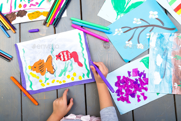 Child drawing. Top view of child hands with pencil painting picture on paper. Kid drawings. - Stock Photo - Images