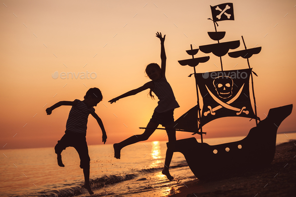 Happy children playing on the beach at the sunset time. - Stock Photo - Images