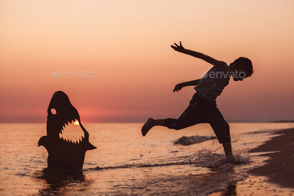 One happy little boy playing on the beach at the sunset time. - Stock Photo - Images