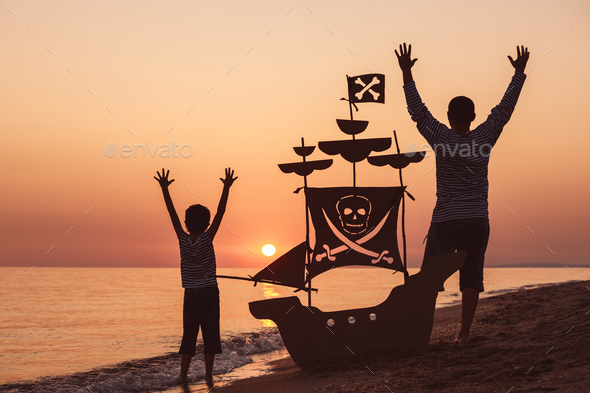 Father and son  playing on the beach at the sunset time. - Stock Photo - Images