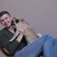 Man Caresses a Cute Pug on a Soft Armchair Indoors - VideoHive Item for Sale
