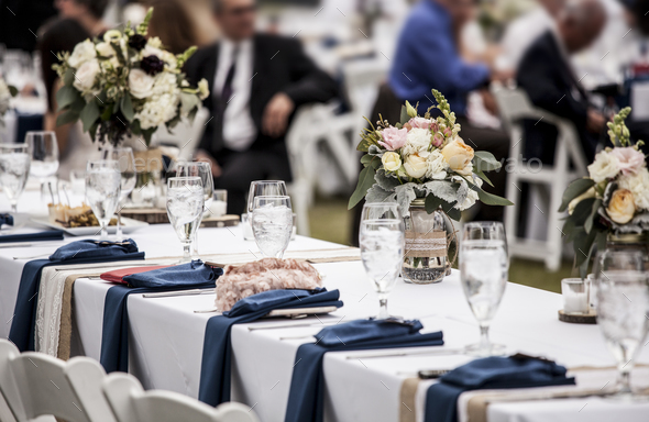 Table set up for wedding reception with people out of focus in b - Stock Photo - Images