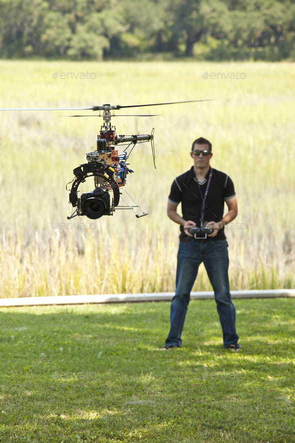 Man controlling helicopter drone, UAV with SLR camera attached. - Stock Photo - Images