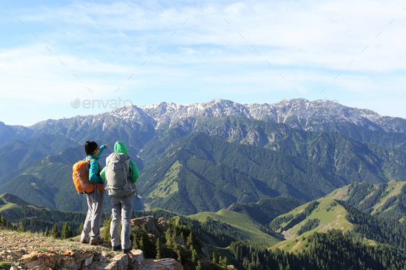 Hiking friends enjoy the view on mountain peak - Stock Photo - Images