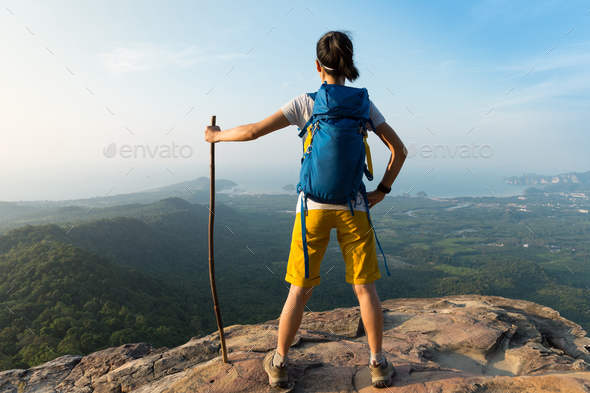 Successful hiker stand on mountain top cliff edge  - Stock Photo - Images