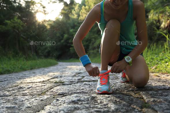 Trail runner tying shoelace on forest trail  - Stock Photo - Images
