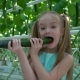 Daughter Eating Cucumbers in the Greenhouse - VideoHive Item for Sale