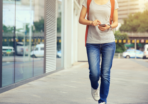 Woman walking and use mobile phone on city street - Stock Photo - Images