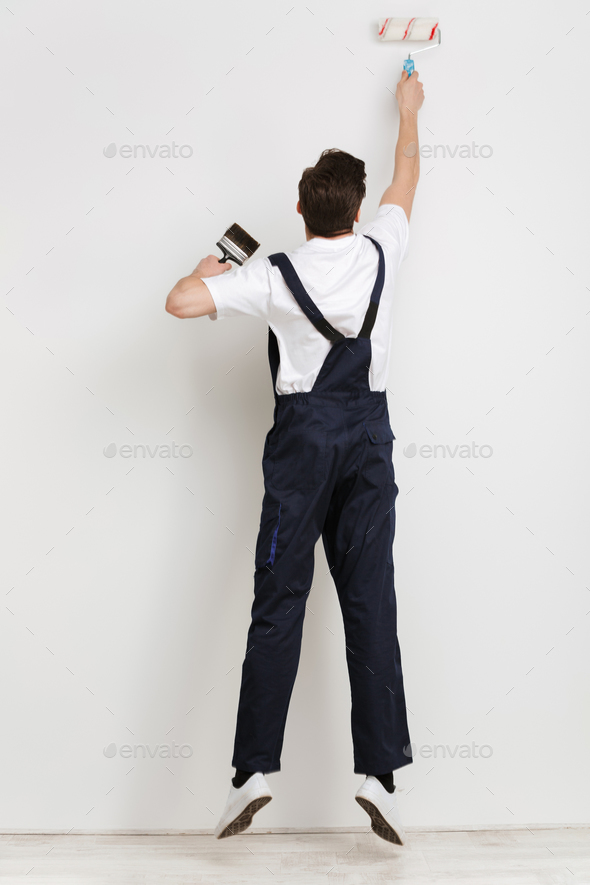 Full length back view of young male builder painting wall - Stock Photo - Images