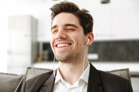 Cheerful young businessman in home listening music - Stock Photo - Images