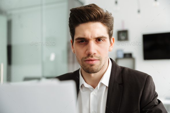 Concentrated young businessman working indoors - Stock Photo - Images