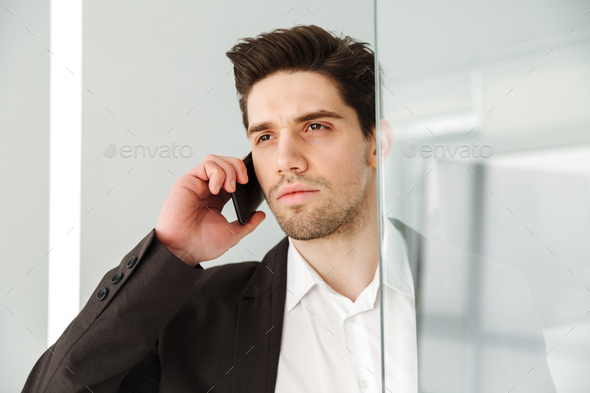 Serious young businessman talking by phone. - Stock Photo - Images