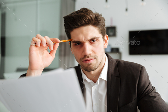 Concentrated young businessman holding documents. - Stock Photo - Images