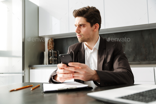 Serious young businessman chatting by mobile phone. - Stock Photo - Images