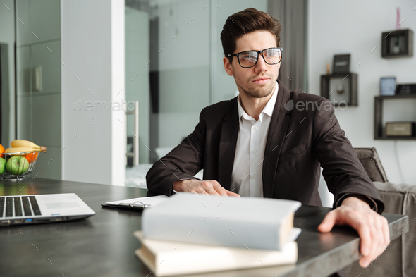 Serious young businessman working indoors - Stock Photo - Images