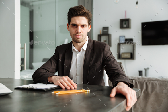 Serious young businessman working indoors. - Stock Photo - Images