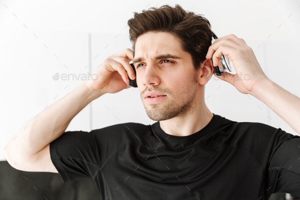 Handsome young man in headphones. Looking aside. - Stock Photo - Images