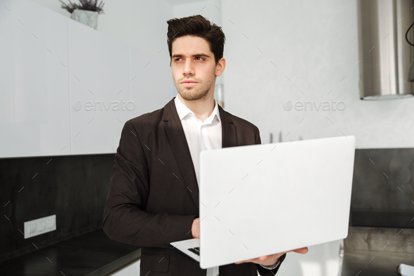 Serious young businessman using laptop computer. - Stock Photo - Images