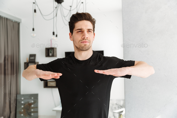 Handsome young man standing in home - Stock Photo - Images