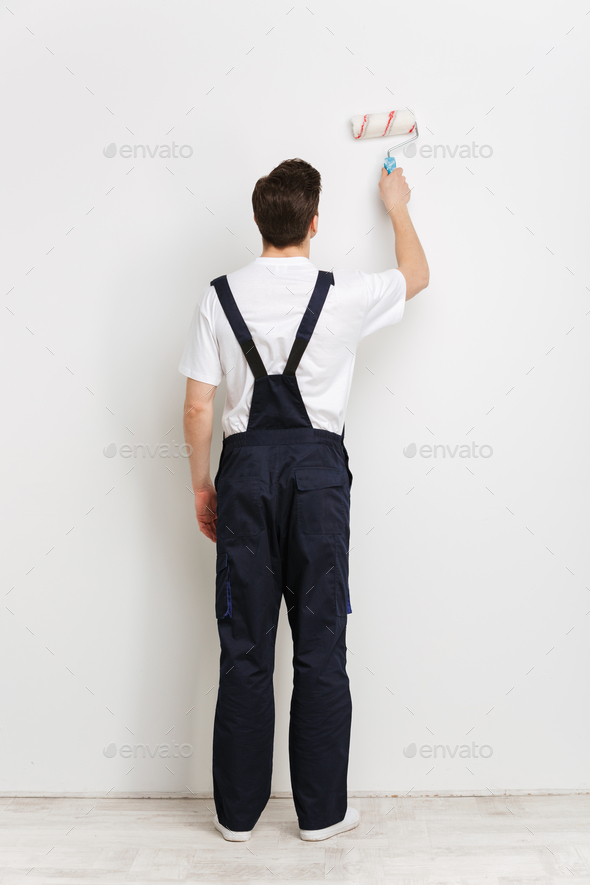 Full back view image of Young male builder painting wall - Stock Photo - Images
