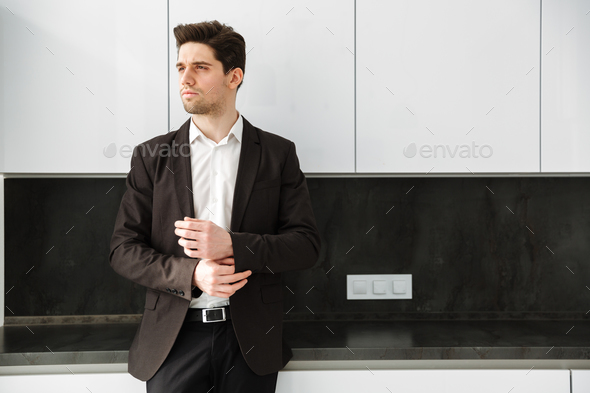 Serious young businessman standing in home - Stock Photo - Images