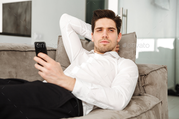Concentrated young businessman in home lies on sofa - Stock Photo - Images