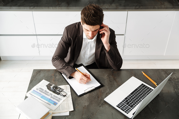 Concentrated young businessman working talking by mobile phone. - Stock Photo - Images