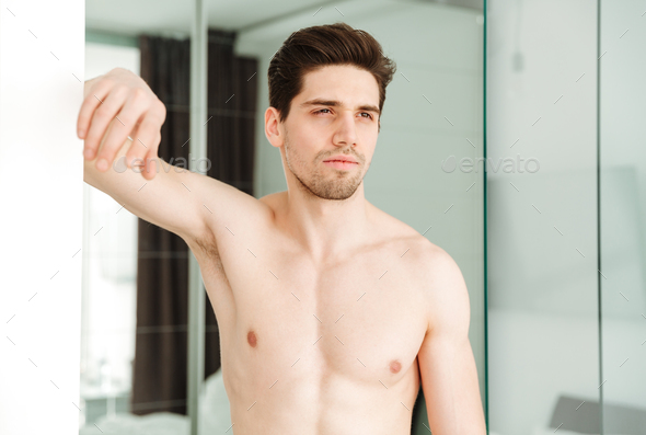 Serious naked man standing in home - Stock Photo - Images